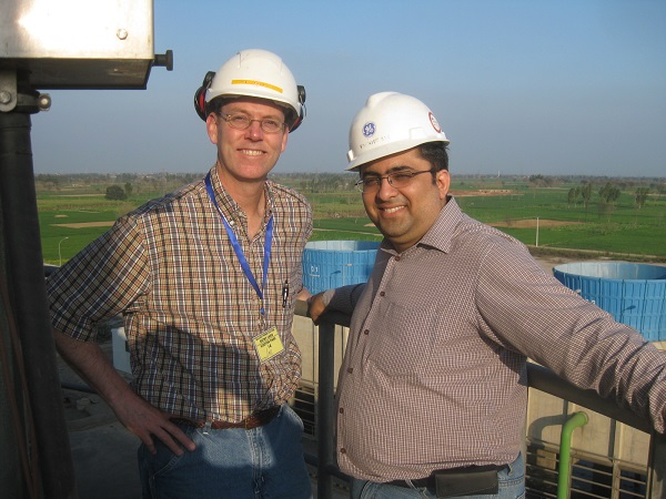 A local engineer from Lahore City in Pakistan at home with his American engineer friend atop the chimney of a modern power plant in rural Pakistan.