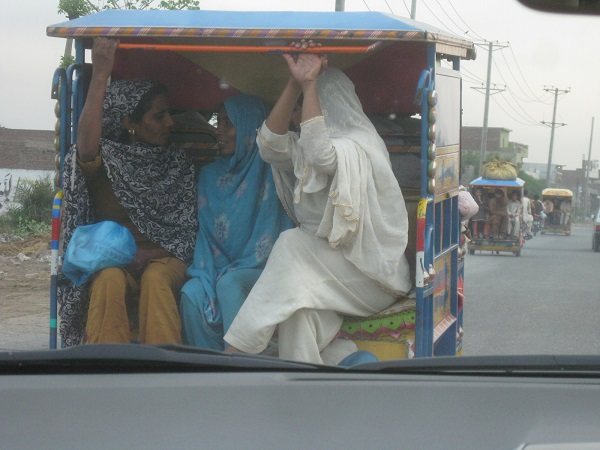 In rural Pakistan, some are lucky to have motorized transportation. In this case, three women in the back of a three-wheeled converted motorbike.